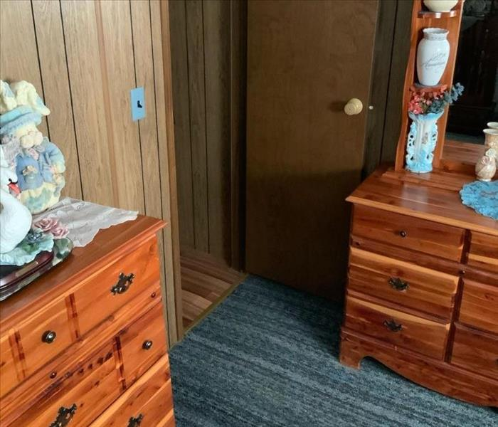 wood chest dresser on wet blue carpet. Brown wood door