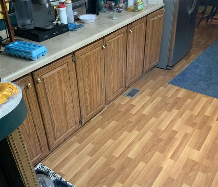 wet brown hardwood flooring and cabinets with white counter top