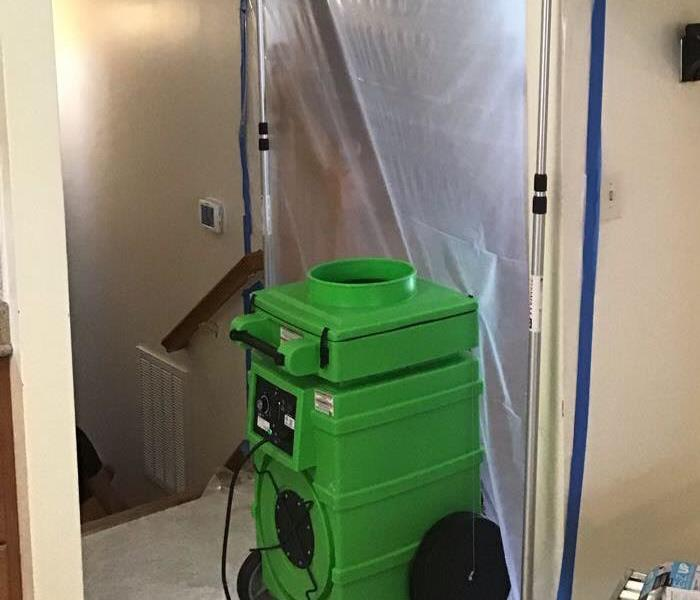 green air scrubber with containment in the back ground of a residential home